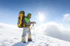 O mochileiro está levantando em montanhas do inverno Imagem de Stock Royalty Free