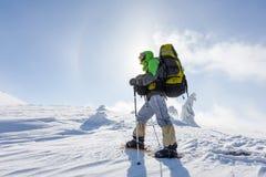 O mochileiro está levantando em montanhas do inverno Fotos de Stock