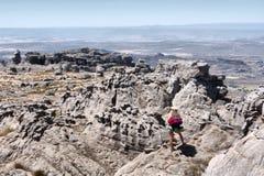 O mochileiro fêmea olha a paisagem da montanha fotos de stock royalty free