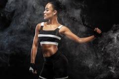 O modelo afro-americano bonito desportivo, mulher no sportwear faz a aptidão que exercita no fundo preto para ficar apto foto de stock