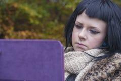 O modelo alternativo sentou-se em um banco com um PC da tabuleta Fotos de Stock