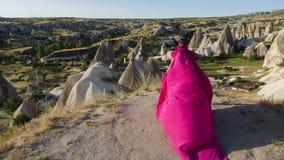 O modelo alto novo da menina corre em um vestido roxo longo com uma cauda nas montanhas filme