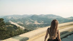 O modelo bonito da jovem mulher com cabelo longo em um vestido longo elegante macio preto está andando ao longo do balcão no filme