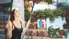 O modelo bonito da menina que balança no close up do balanço, cabelo no vento torna-se e sorrir filme