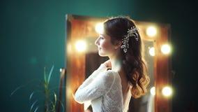 O modelo bonito de uma noiva gerencie na frente de um espelho, endireita seu vestido de casamento com suas mãos e agarra-se video estoque