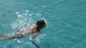 O modelo caucasiano bonito, jovem mulher está nadando em uma associação com água azul em um hotel, sob o céu aberto O conceito filme