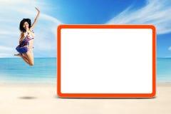 O modelo com bolsa pula na costa perto de uma placa Imagens de Stock Royalty Free