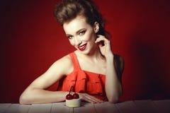O modelo com penteado criativo e coloridos bonitos compõem o assento na tabela de madeira com a pastelaria deliciosa da cereja ne Fotos de Stock