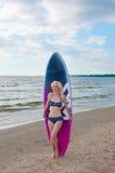 O modelo consideravelmente louro da menina gosta de Marilyn Monroe com placa surfando em uma praia fotografia de stock