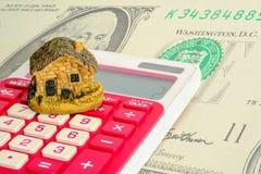 O modelo da casa está na calculadora com fundo do dólar Empréstimos de bens imobiliários ou para salvar o dinheiro para comprar a fotos de stock royalty free