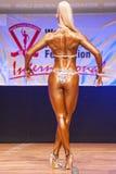 O modelo da figura fêmea mostra seu melhor no campeonato na fase Imagens de Stock Royalty Free