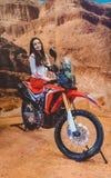 O modelo da menina mostra uma bicicleta de Enduro do modelo novo Suporte com inovações da motocicleta imagem de stock