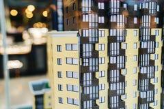 O modelo de um condomínio do apartamento Uma construção do multi-andar com janelas e um balcão marrom imagens de stock