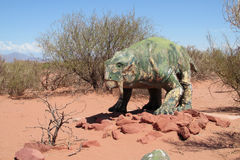 O modelo de um dinossauro na areia imagem de stock