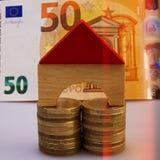 O modelo de uma casa de madeira senta-se em pilhas de euro- moedas no backg Fotografia de Stock