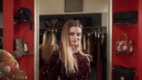 O modelo demonstra o vestido que escolheu, a senhora vestiu a roupa brilhante e brilhante vídeos de arquivo