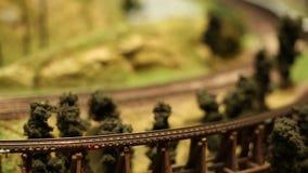O modelo diminuto Scale Railway, trem com vagões está conduzindo, movimento borrado filme
