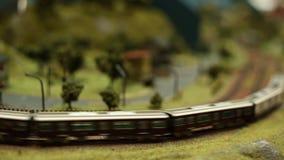 O modelo diminuto Scale Railway, trem com vagões está conduzindo, movimento borrado video estoque