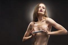 O modelo em topless atlético magro bonito da menina realiza em suas mãos imagem de stock royalty free