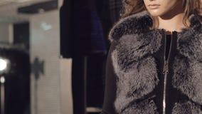 O modelo esperto está na pose nos casacos de pele ricos para anunciar lentamente filme