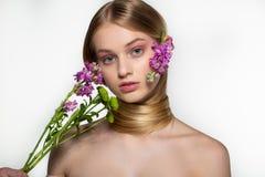 O modelo f?mea novo bonito com olhos azuis, pele perfeita com as flores no ombro, seu pesco?o ? envolvido no cabelo foto de stock royalty free