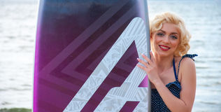 O modelo gosta de Marilyn Monroe com placa surfando fotos de stock