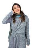 O modelo lindo de sorriso com inverno veste a fatura de ges do telefonema Foto de Stock Royalty Free
