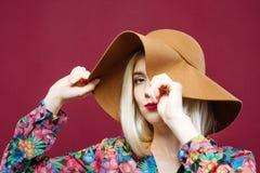 O modelo louro está cobrindo um olho pelo chapéu elegante A mulher bonita na camisa colorida está levantando no fundo cor-de-rosa Foto de Stock