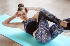 O modelo magro da aptidão está exercitando no assoalho em uma esteira verde da ioga foto de stock