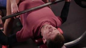 O modelo muito bonito e 'sexy' da aptidão ajuda a executar a imprensa de banco para um homem no gym filme