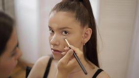 O modelo tem uma composição pelo maquilhador no salão de beleza Primeira opini?o da pessoa Modelo do ruivo com sardas Feche acima video estoque