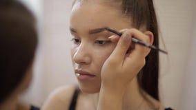O modelo tem uma composição pelo maquilhador no salão de beleza Primeira opini?o da pessoa Modelo do ruivo com sardas Feche acima filme
