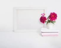 O modelo vazio branco do quadro de madeira com uma peônia floresce o ramalhete em um copo da porcelana e em uma pilha dos livros  Foto de Stock Royalty Free