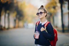 O moderno bonito adolescente com saco vermelho bebe o milk shake de uma rua de passeio do copo plástico entre construções Menina  imagem de stock royalty free