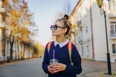 O moderno bonito adolescente com saco vermelho bebe o milk shake de uma rua de passeio do copo plástico entre construções Menina  fotografia de stock royalty free