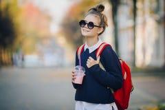 O moderno bonito adolescente com saco vermelho bebe o milk shake de uma rua de passeio do copo plástico entre construções Menina  imagens de stock