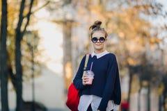 O moderno bonito adolescente com saco vermelho bebe o milk shake de uma rua de passeio do copo plástico entre construções Menina  foto de stock royalty free
