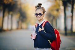 O moderno bonito adolescente com saco vermelho bebe o milk shake de uma rua de passeio do copo plástico entre construções Menina  fotografia de stock