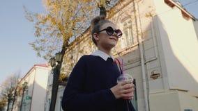O moderno bonito adolescente com saco vermelho bebe o milk shake de uma rua de passeio do copo plástico entre construções Menina  video estoque