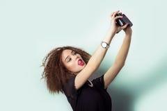 O moderno bonito da moça toma fotos, dispara no selfe, tomando imagens dsi mesmo na câmera nas calças de brim e em um t-shirt pre Fotos de Stock