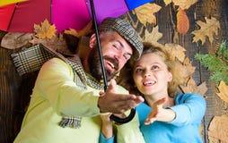 O moderno com barba e a menina alegre esperam o guarda-chuva colorido da posse chuvosa do tempo Obstáculo chuvoso do tempo não pa fotos de stock