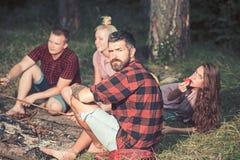 O moderno com barba relaxa com os amigos no homem farpado da floresta na camisa de manta na natureza O turista aprecia acampar ve fotografia de stock