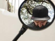 O moderno com uma barba e um tampão toma imagens dsi mesmo no espelho de uma motocicleta imagem de stock royalty free
