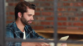 O moderno de sorriso equipa usando uma tabuleta e sorvendo o café vídeos de arquivo