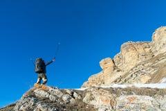 O moderno do caminhante com uma grande trouxa no pé das rochas épicos declara a intenção ganhar Fotos de Stock Royalty Free