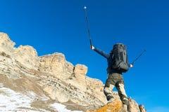 O moderno do caminhante com uma grande trouxa no pé das rochas épicos declara a intenção ganhar Foto de Stock Royalty Free