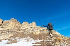 O moderno do caminhante com uma grande trouxa no pé das rochas épicos declara a intenção ganhar Fotos de Stock