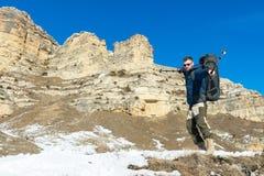 O moderno do caminhante com uma grande trouxa no pé das rochas épicos declara a intenção ganhar Fotografia de Stock Royalty Free