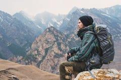 O moderno farpado cansado com os binóculos em suas mãos senta-se em uma pedra entre as montanhas e olha-se para fora na distância Imagens de Stock Royalty Free