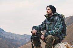 O moderno farpado cansado com os binóculos em suas mãos senta-se em uma pedra entre as montanhas e olha-se para fora na distância Imagem de Stock Royalty Free